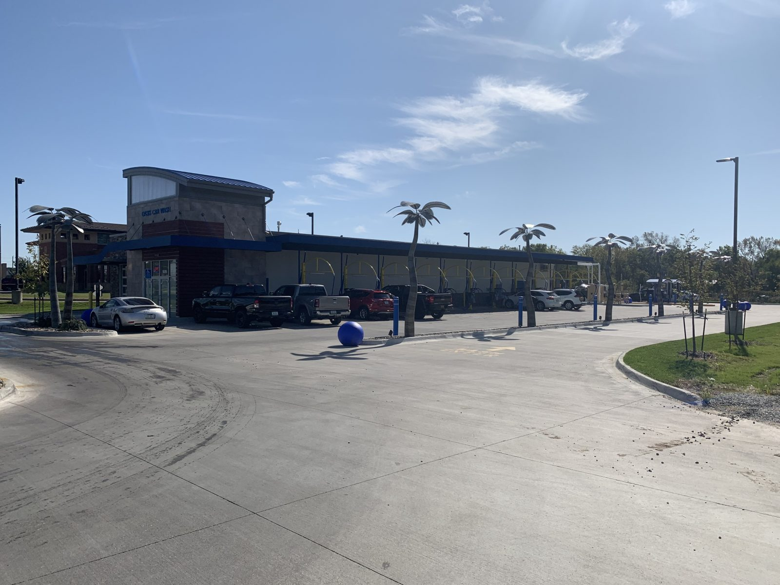 Cars are lined up at Oasis car wash on a beautiful day